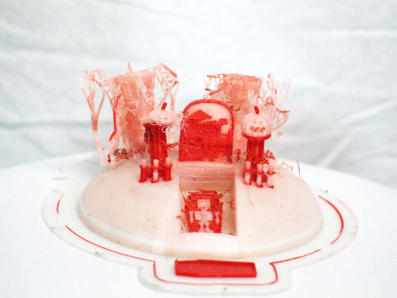 A 3D print of a Halloween scene, with two decaying trees a gravestone in front of them. A jack-o-lantern on a pedestal on either side, each has three candles in front of them. In front of the gravestone is an open grave with an open casket. In the casket is a skeleton and the casket lid is in front of the entire scene.