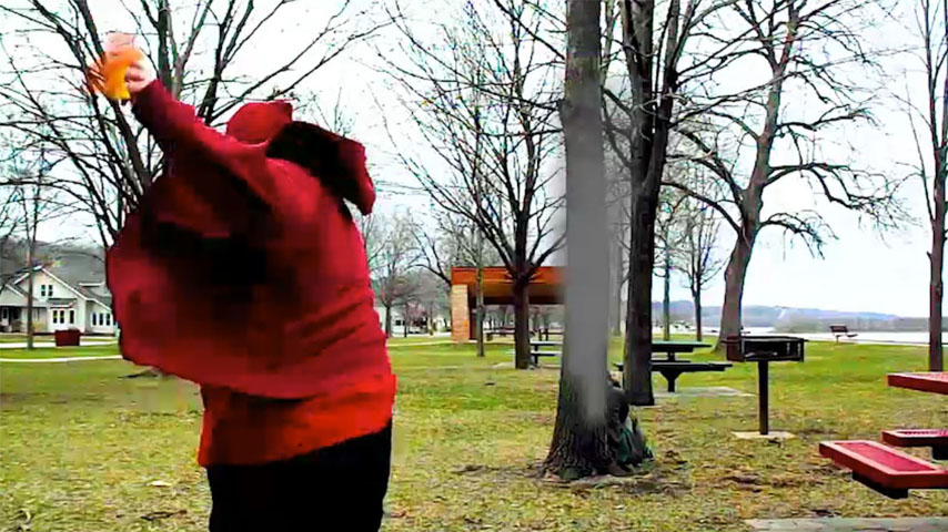 A person throwing a fireball at another person hiding behind a tree.